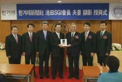 SGI-Korea General Director Yeo Sang Rak (4th from left) receives plaque on behalf of the SGI President and Mrs. Ikeda from CEO Chung (3rd from right)