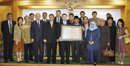 Chair Ade (foreground, 6th from right) entrusts award for Mr. Ikeda to his son Hiromasa (foreground, 6th from left)